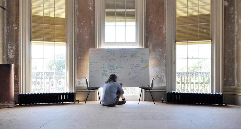 Danny making notes on a whiteboard while sat by the window in the setting of the unrestored drawing room of The Regency Town House
