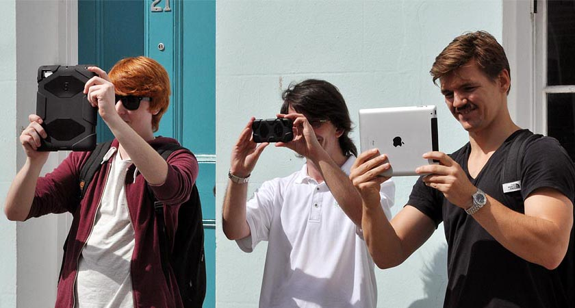 Alex, Simon and Seb, each holding up a mobile device while testing the VisAge prototype app.