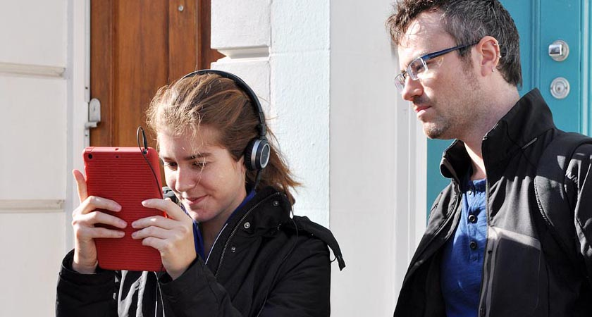 Ana Moutinho testing a VisAge prototype on red tablet device while Will Steptoe observes.