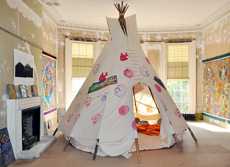 Photgraph of a teepee in the drawing room of a large Regency house, with colourful, patterned artworks on the walls