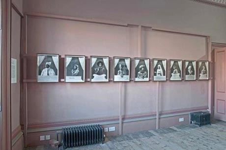 Photo showing dining room wall, with wooden frame supporting a row of black and white photo portraits.