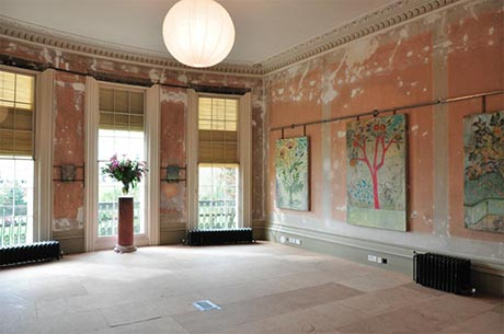Drawing room west wall with three large sash windows.
