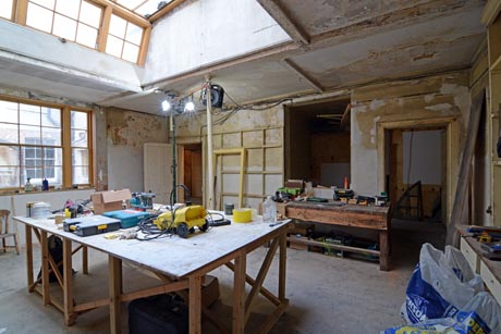 View of kitchen undergoing restoration showing work table and restored window.