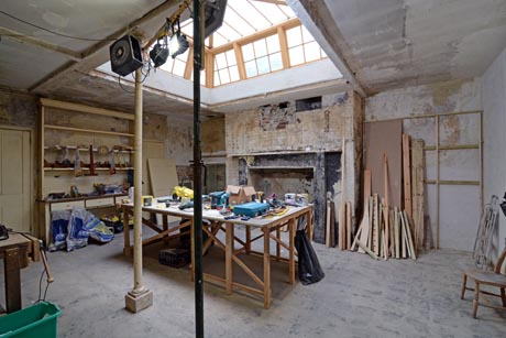 View of kitchen undergoing restoration showing fireplace and original shelves.